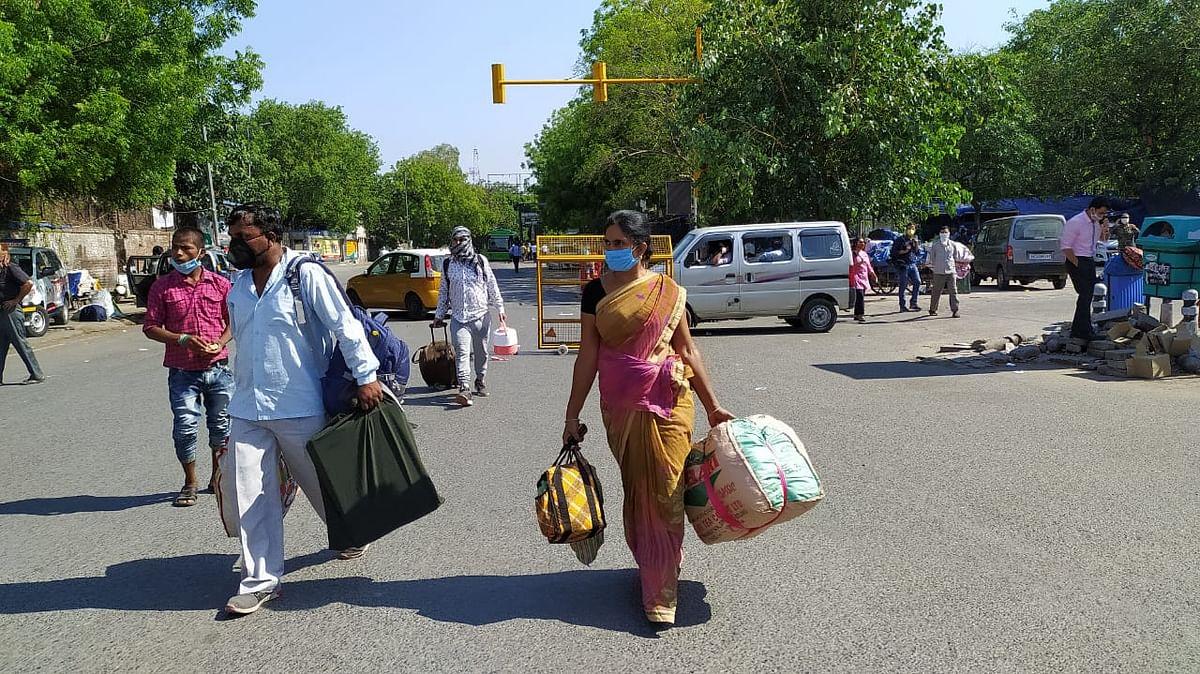 हाथों में सामान लेकर पैदल स्टेशन आते लोग