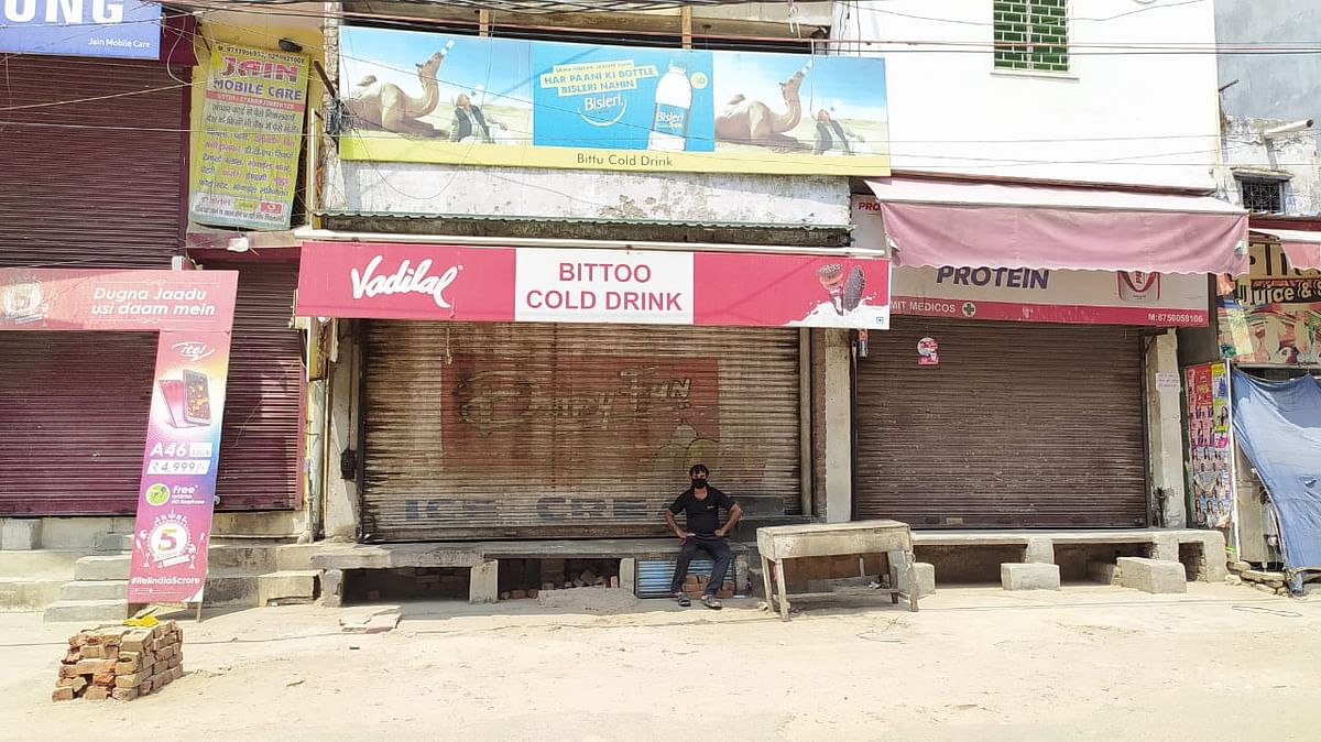 बंद दुकान के बाहर बैठा एक युवक