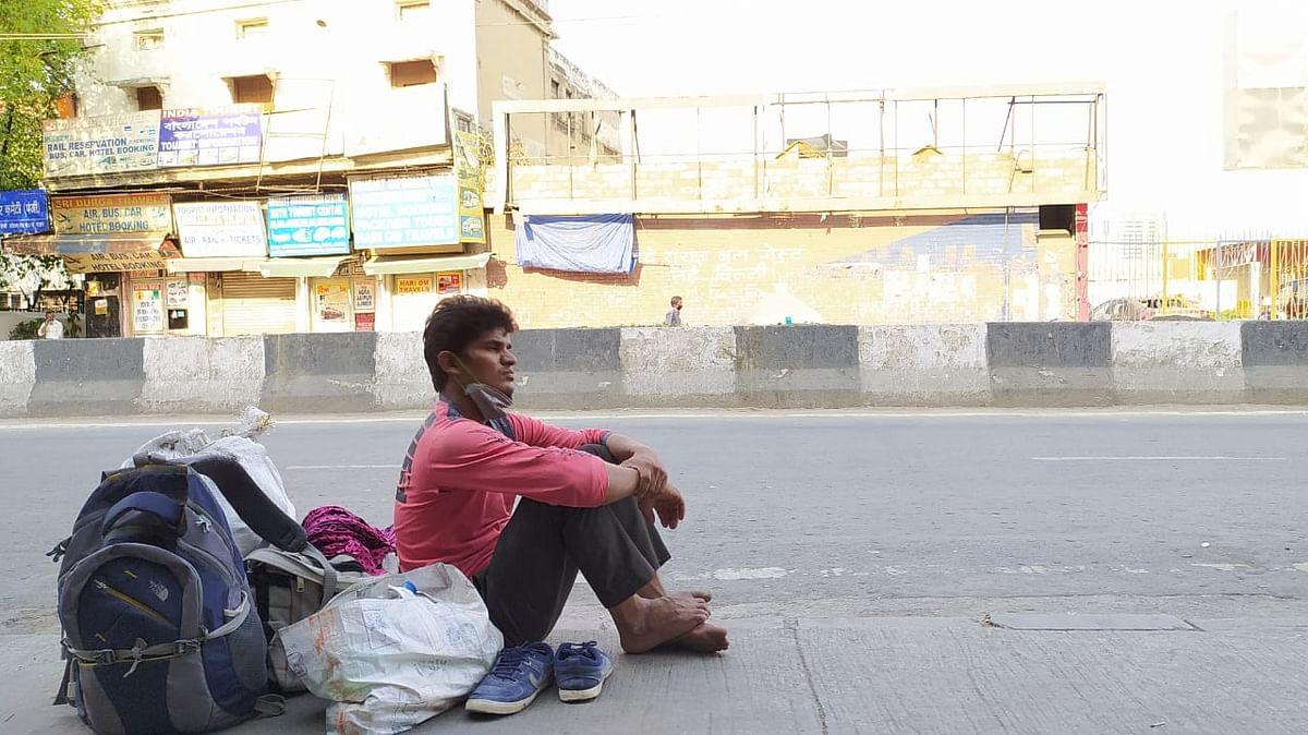 सड़क पर बैठा मजदूर, अपनी बारी आने का इंतजार करते हुए