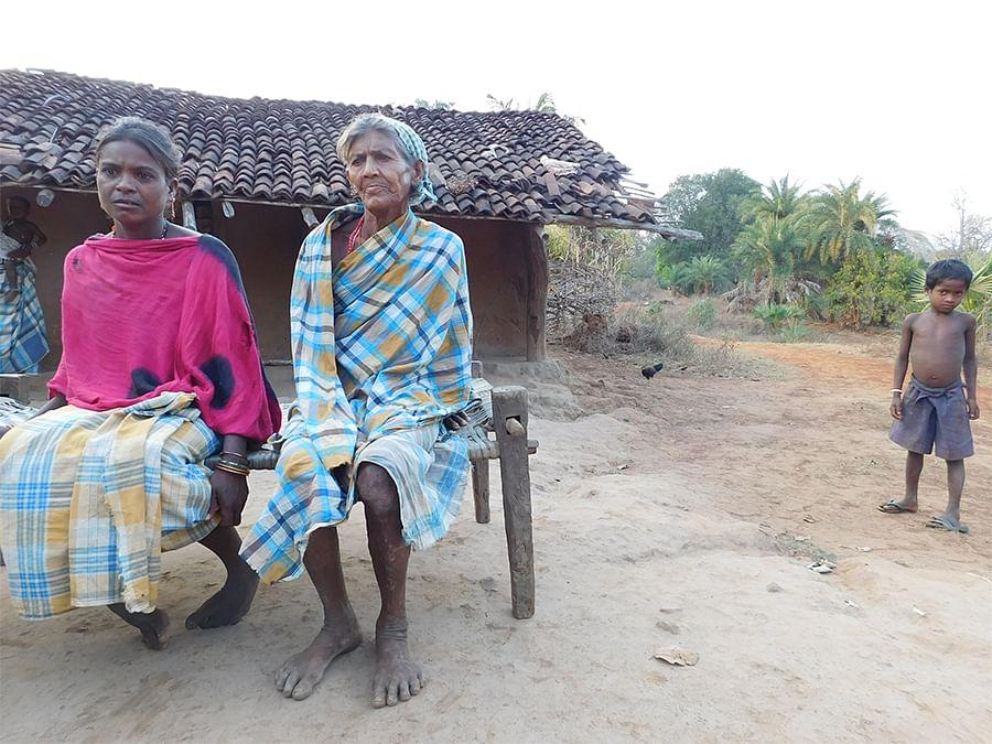 Mandavi Podia Lakka's wife and mother outside their home at Gurrepara.