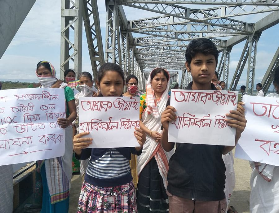 Children from Natun Gaon hold up posters that read 'Let us live'