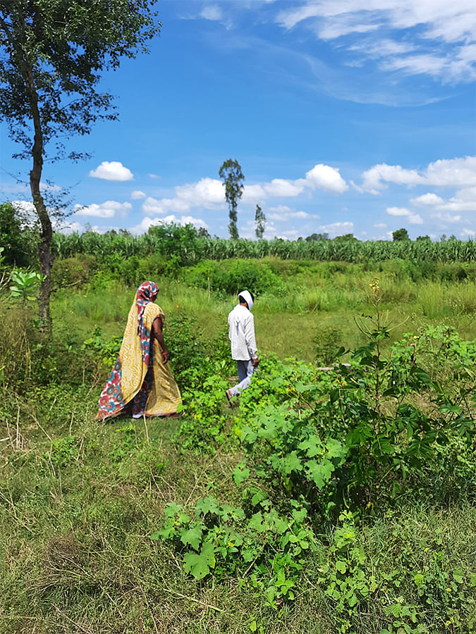 Neha's parents walking towards the dry pond where she was found.