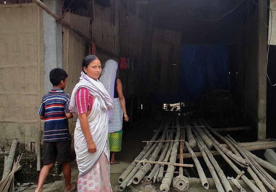 Lokhima Baruah outside her damaged house.