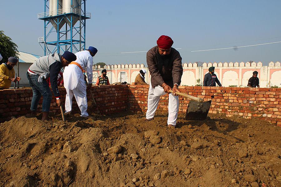 Patinder Singh clears the soil at Baba Ram Singh's funeral site at the Nanaksar gurudwara.