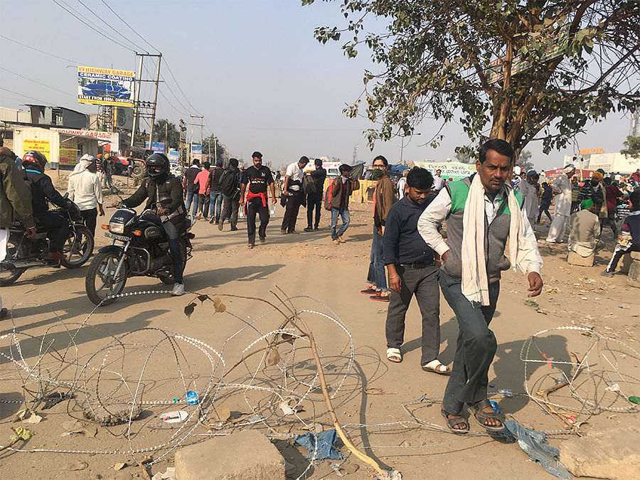 Commuters walk through concertina wire put by security forces on the Delhi-Haryana border to barricade the protests.