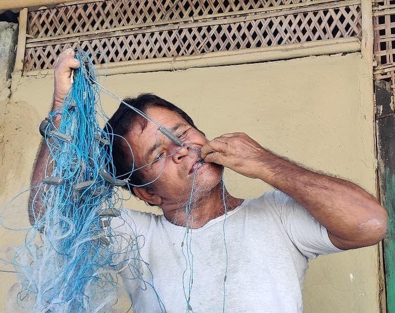Phukan Das untangles his fishing net.