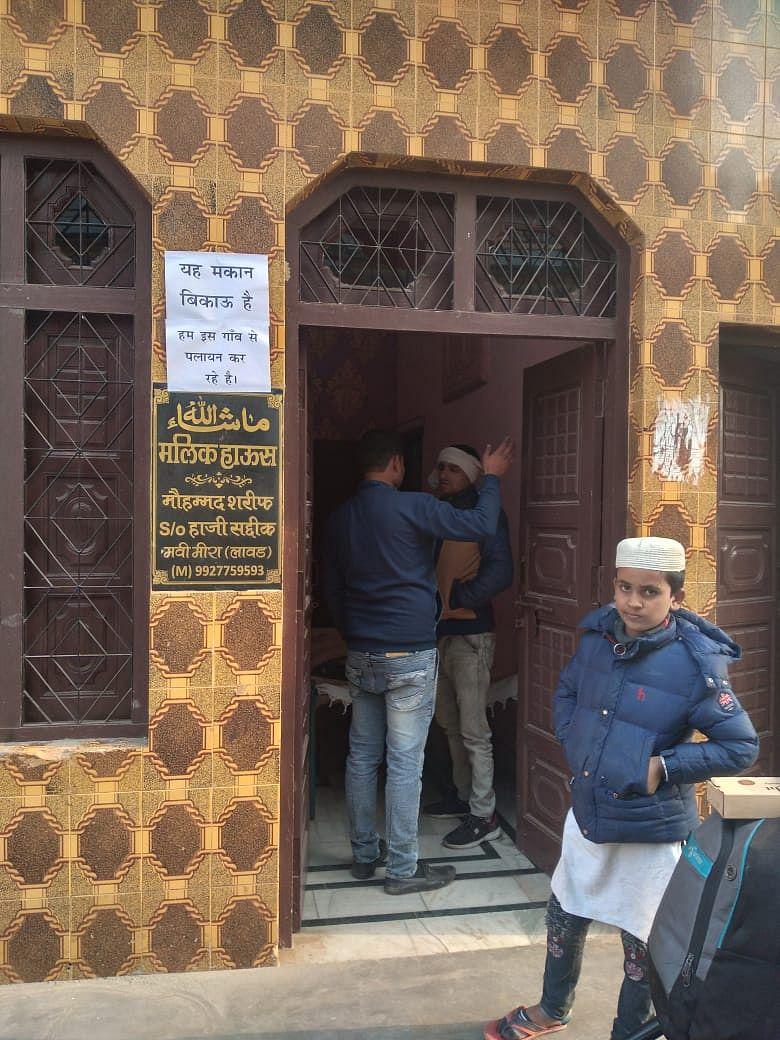 मावी-मीरा गांव में घर पर लगा मकान बिकाऊ का पोस्टर