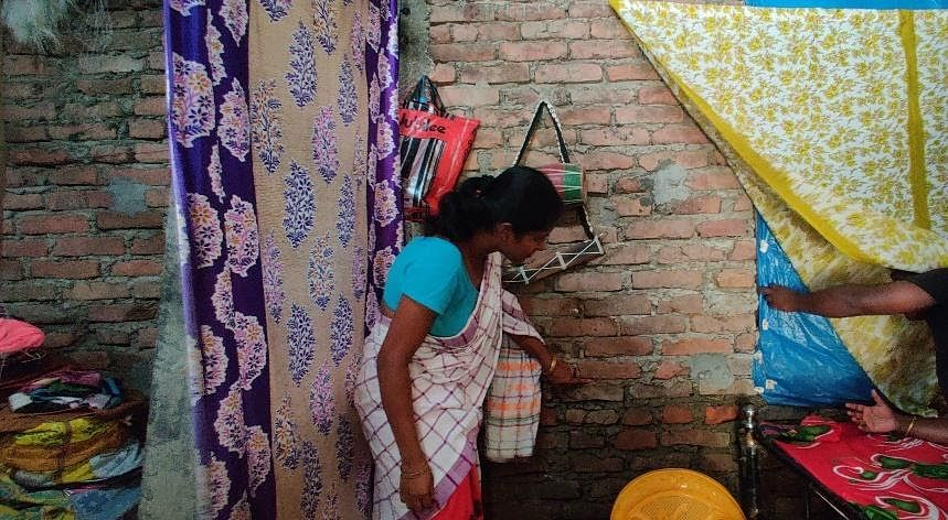 Nilakhi Das points to a mark left by the floodwaters on her wall.