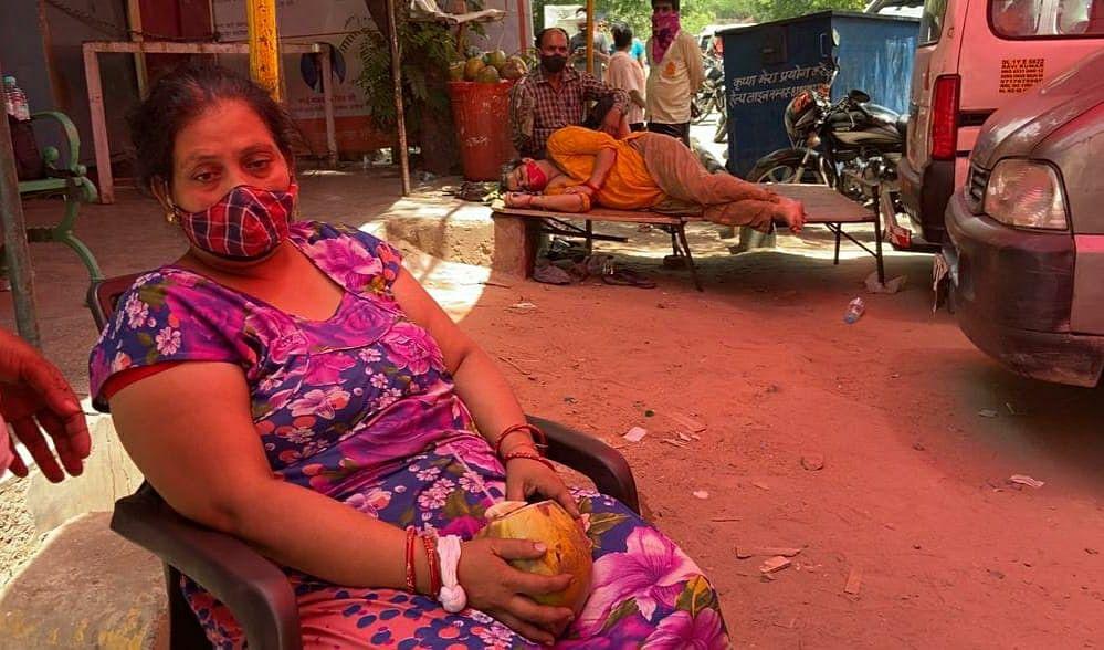 आक्सीजन के इंतजार में बैठी एक महिला