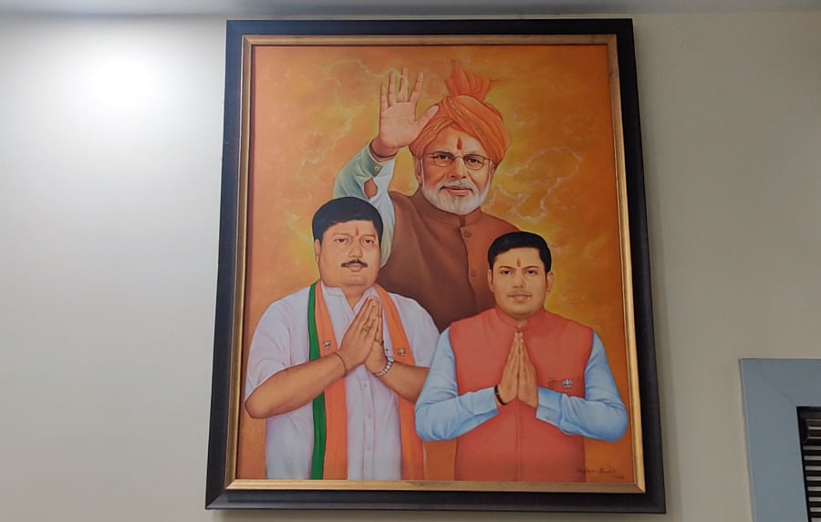 A portrait of Arjun Singh (left) and his son Pawan Singh with Narendra Modi at the Singhs' office.