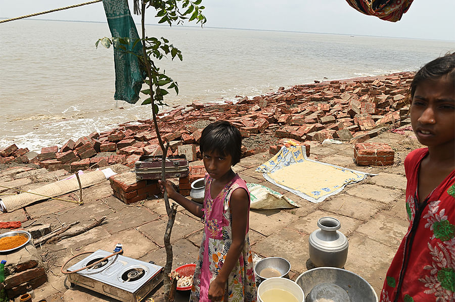 A girl's family pitches a temporary camp on the embankment. Cooking and washing is done in the scorching sun while the Ganges roars a few feet below.