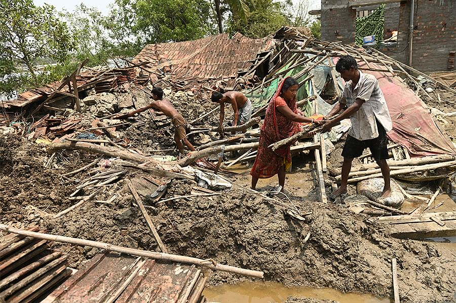 A family tries to salvage the remains of their buried home near Baghdanga Bazar.
