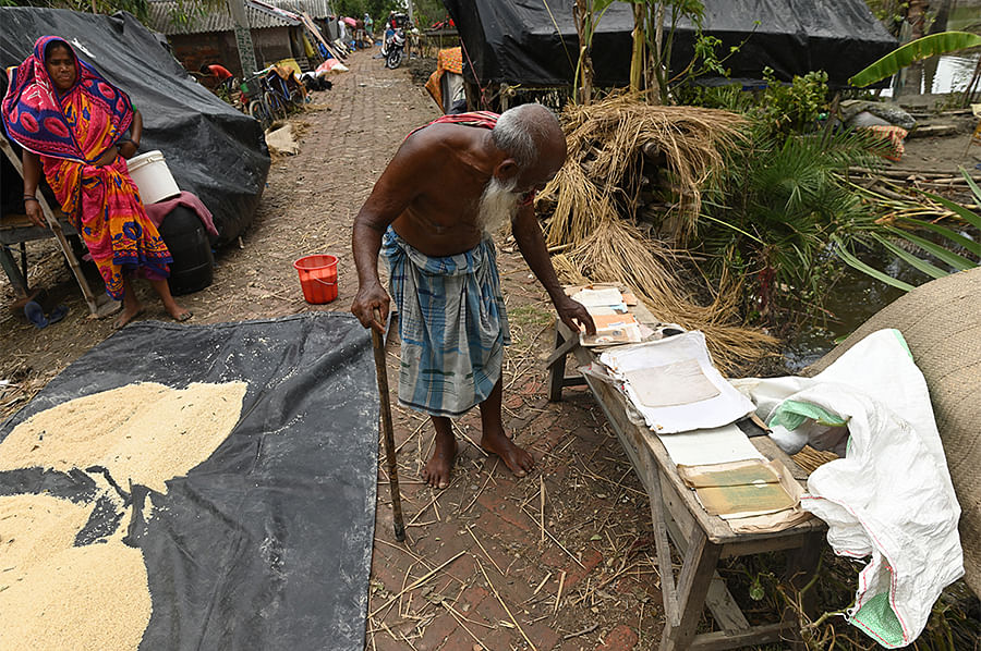 Sk. Nuruddin, 90, tries to dry important documents spanning generations while his daughter-in-law attempts to salvage rice that had been stored for year-long consumption.