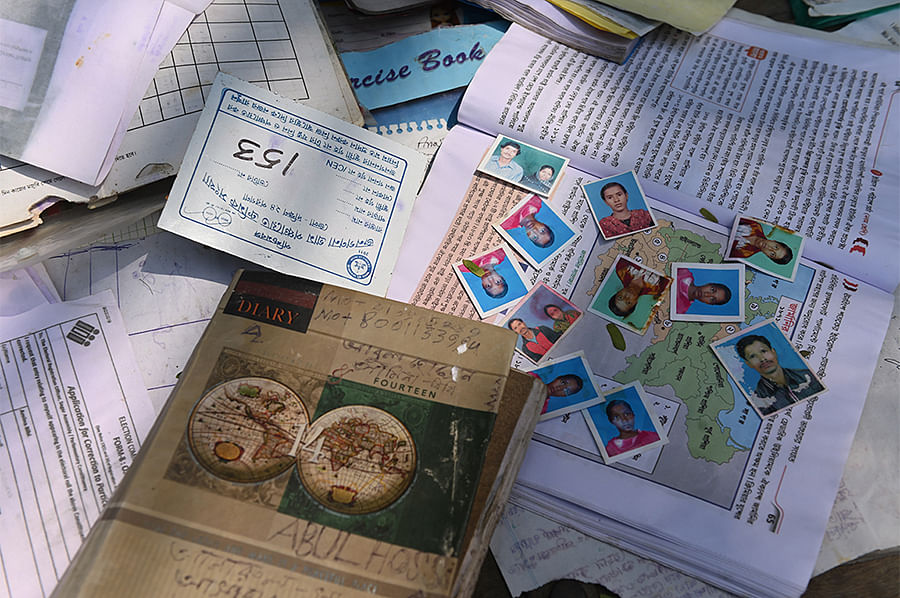 Amina Bibi managed to retrieve some of her textbooks and study material from the water. She spreads them out to dry, placing stained photographs over a map of Germany.