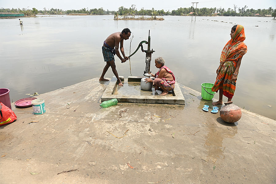People use a hand pump that somehow remained above the floodwater level.