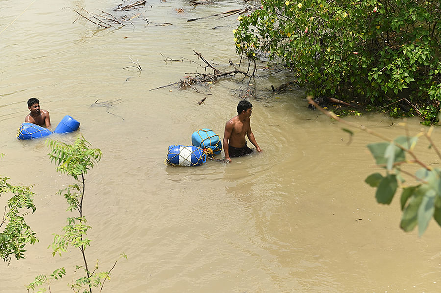 Young men wade through flooded fields to fetch drinking water. Since 30 percent of tubewells in Mousuni now pump out saline water, the shortage of drinking water has become a crisis.
