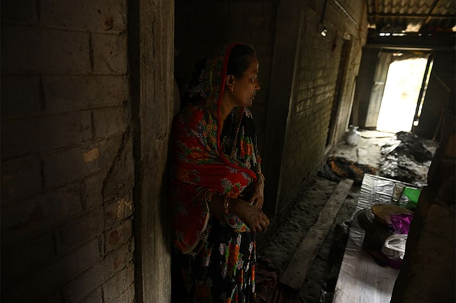 Nafisa and her husband used money from the rural housing scheme to build a house with concrete walls and a roof. They moved into their home in March. The flood on May 26 tore apart the interiors. Standing in ankle-deep mud, Nafisa can't stop crying.