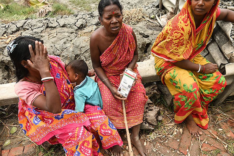 Beside a village road near Maipith Coastal, Putul Mudi sits with her daughter's Aadhaar card, begging passersby to help her fill an application form for compensation.