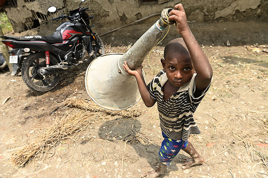 At a village near Jamtala in Kultali Block, a boy uses the empty shell of a discarded amplifier to announce that food will be served in a community kitchen.