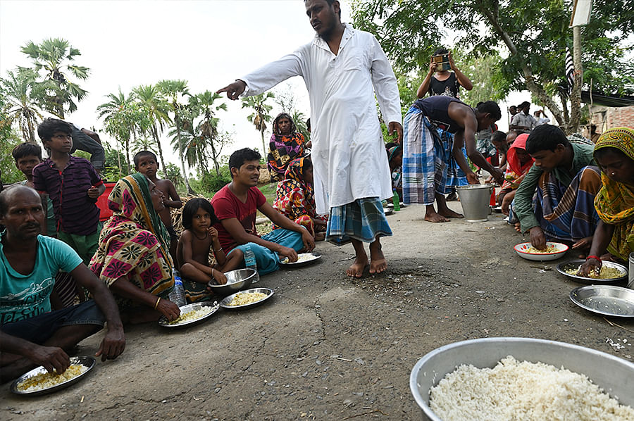 At Gazipur, near Maipith Coastal, an organisation feeds villagers on an open road. Though the Sundarbans was never an affluent economy, it has not seen scenes like this before 2020.