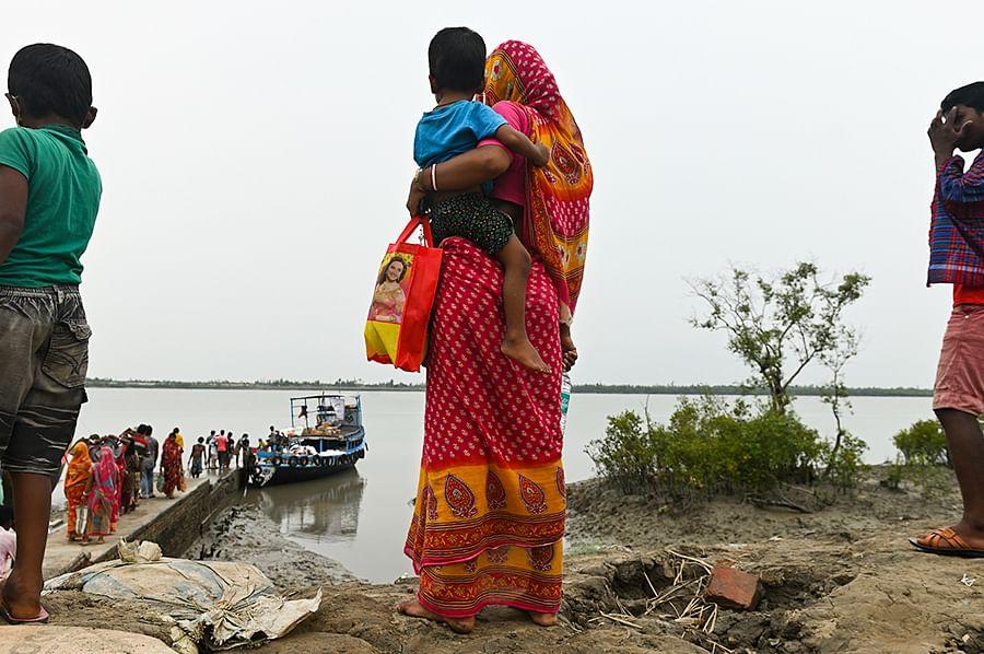 A family waits for food on an embankment in Rakaskhali island.