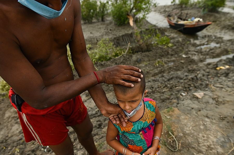 A child and her father gaze at a landscape of wreckage and mud in Brajaballavpur island.