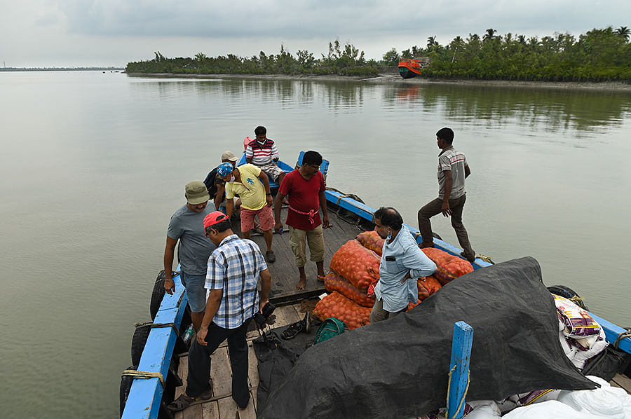Members of MAA, a civil society, sail through a maze of rivers and creeks to distribute food ration among villagers of Brajaballavpur island. To reach nearly any island in the Sundarbans, one needs to make a long journey by boat.