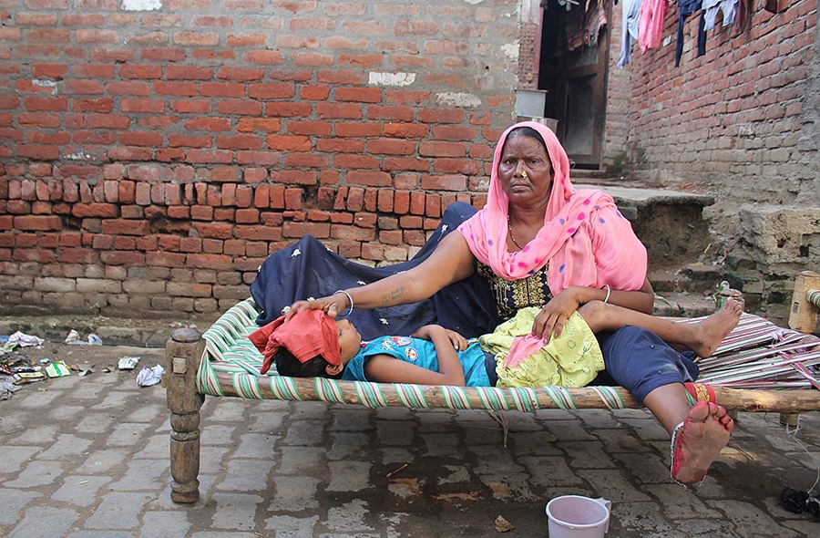 Reshma with an ill Virat, 4, and Tanya, 10, outside her Sudama Nagar house.