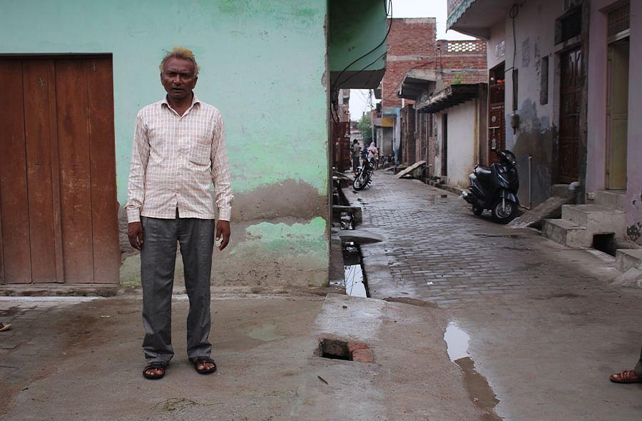 Birendra Singh Savita on the drain cover in Sudama Nagar built before the CM's visit.
