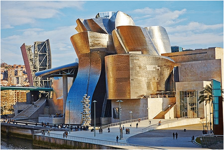 """Guggenheim Museum Bilbao, Spain. The Guggenheim's satellite in Bilbao, Spain, multiplied the museum's exhibition space in a mountain of stone, glass, and titanium that follows the contours of the Nervión river. It's one of the most admired works of contemporary architecture, the building has been hailed as a """"signal moment in the architectural culture"""", because it represents """"one of those rare moments when critics, academics, and the general public were all completely united about something""""."""