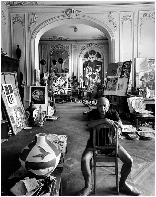 Portrait of Italian painter Pablo Picasso. Newman uses a wide-angle lens in this photograph to showcase the entire room containing Picasso's artwork. While the first focal point of interest is Picasso himself, the eye slowly moves around the room exploring it. This photograph also uses strong shapes, depth and symmetrical elements to make it more aesthetically appealing.