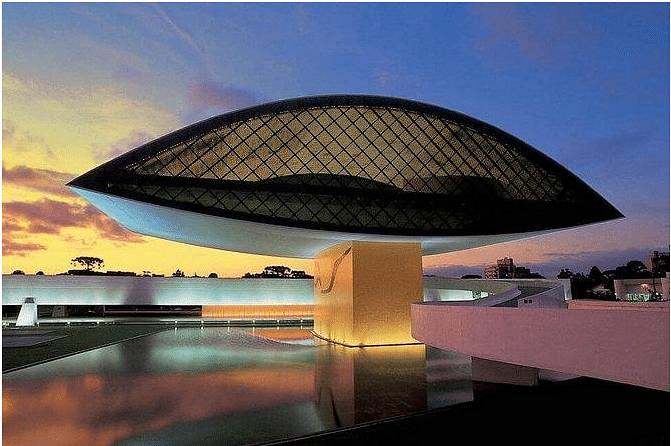 Museu Oscar Niemeyer in Brazil is reminiscent of a human eye and fundamentally gave the museum a new identity. The building was completed and opened to the public in 2003, and the Novo Museu was renamed the Oscar Niemeyer Museum in the same year. Constructed of reinforced concrete, the idiosyncratic, 30-meter tall structure sits above a pool of water and is connected to the main museum building by a futuristic underground walkway.