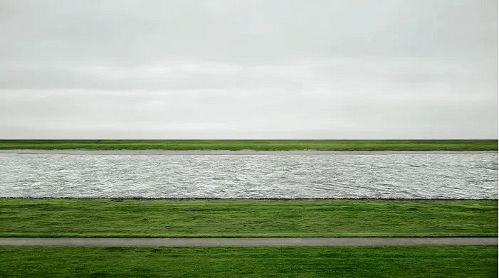 Rhine II. By joining photographs of different segments of the river Rhine, Gursky in Rhein II, measuring 5 × 10 feet, created a nonexistent section of the Rhine River, and recreated a completely new landscape, free of industry and human presence. The outcome was a composition of astonishing colour and precise geometry, resembling a colour-field painting. Rhein II sold at Christie's New York, for $4.3 million, making it the most expensive photograph ever sold.