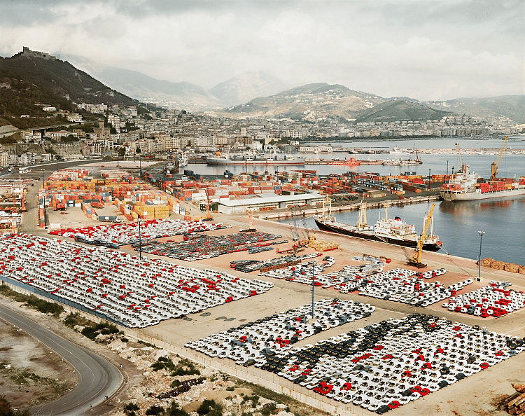 Salerno I. Gursky tells that he was overwhelmed by what he saw from this photo due to the complexity of the elements in it. There are leading lines that lead the eye from the bottom left of the frame towards the center and finally towards the horizon with mountains. There is symmetry and contrasting colours (of the cars) that create a visual interest in the photograph.
