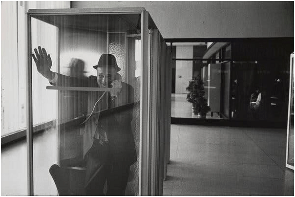 This photo captures the emotion of the man speaking inside a phone booth. The photograph follows the rule of thirds where the key elements (the man) in a photograph are placed in the location where the horizontal and vertical lines dividing the images into equal parts intersect.