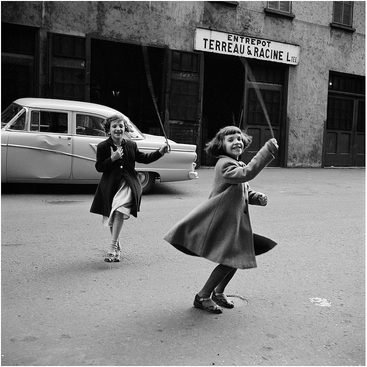 This photograph clearly communicates the joy felt by two kids playing in the street. The frame is slightly tilted giving a sense of tension as the kids are twirling or dancing. The sign on the building and the car gives a sense of location.