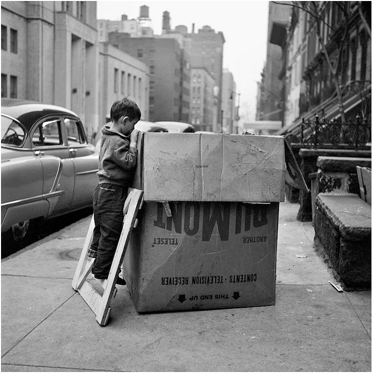 In this photograph of a young boy curiously exploring a large box, the size of the box adds visual weight. The buildings on either side act as leading lines further pulling the viewers attention towards the center of the frame.