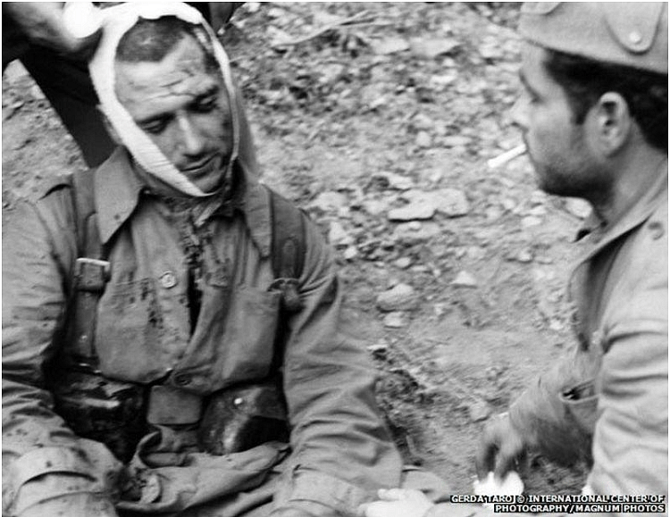 Republican soldiers on the Segovia front, 1937. This photo captures the state of soldiers during the war. Despite getting injured they're still expected to fight till the very end. The soldier on the right is looking towards the injured soldier further drawing the viewer's eyes towards the latter.