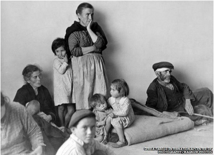 Refugees from Malaga in Almeria, 1937. In this photograph the direction in which the eyes of the refugees are pointing creates sense of tension. The two elderly women, the baby and the man are looking towards the right whereas the two other kids are looking towards the left. In the center there is a boy looking directly into the camera which catches the viewer off guard. The posture of the man on the right acts as a guiding curve towards the center of the frame.