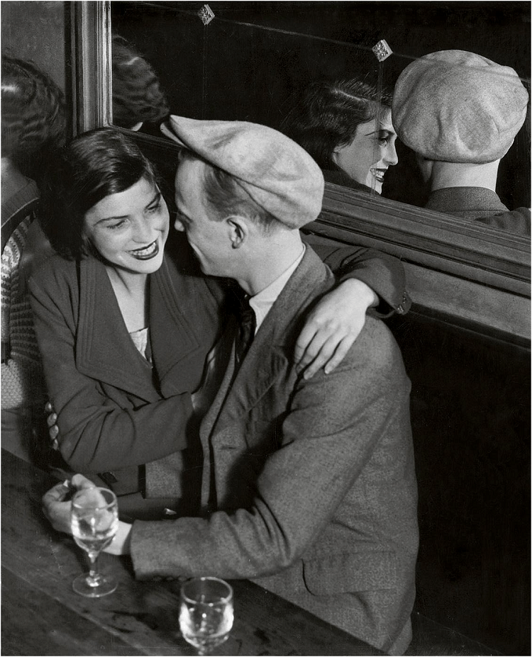Bal des Quatre Saisons, rue de Lappe. c. 1932. In this photograph of a romantic couple, the context of the place where they are is set by the wine glasses and their dressing. The expression of the woman takes importance and we see her face also in the mirror behind them. The diagonal lines caused by the table and the mirror add depth while the curved position of their hands ensures the eye circles around them.