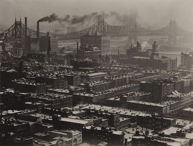 From 'Room 3003' - The Shelton, New York, Looking Northeast, 1927. This photo documents the constant state of change and development of the city. The composition causes the buildings to appear in a zig-zag pattern leading to the horizon which has smoke blowing towards the direction of the bridge.
