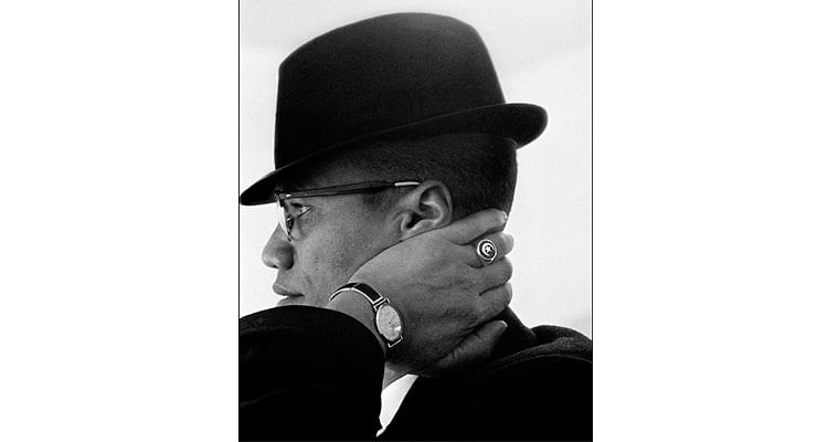 Malcolm X, 1960. This photograph conveys, through its interesting composition, how Malcom X carried himself and the way he dressed. The photo uses strong contrasts to highlight the subjects face and his key characteristics like his hat, ring, watch and suit.
