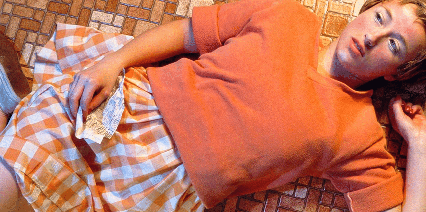 Untitled#96 – Sherman dressed up as a teenage girl in this photograph lying on the floor, clutching a page torn from a newspaper. The girl does not meet the viewer's gaze but instead looks off into the middle distance, as if distracted or daydreaming of something. However, her schoolgirl naivety is contrasted by her freshly painted blood red nails, heavily highlighted cheeks and bright red lipstick - all signs of growing sexuality.