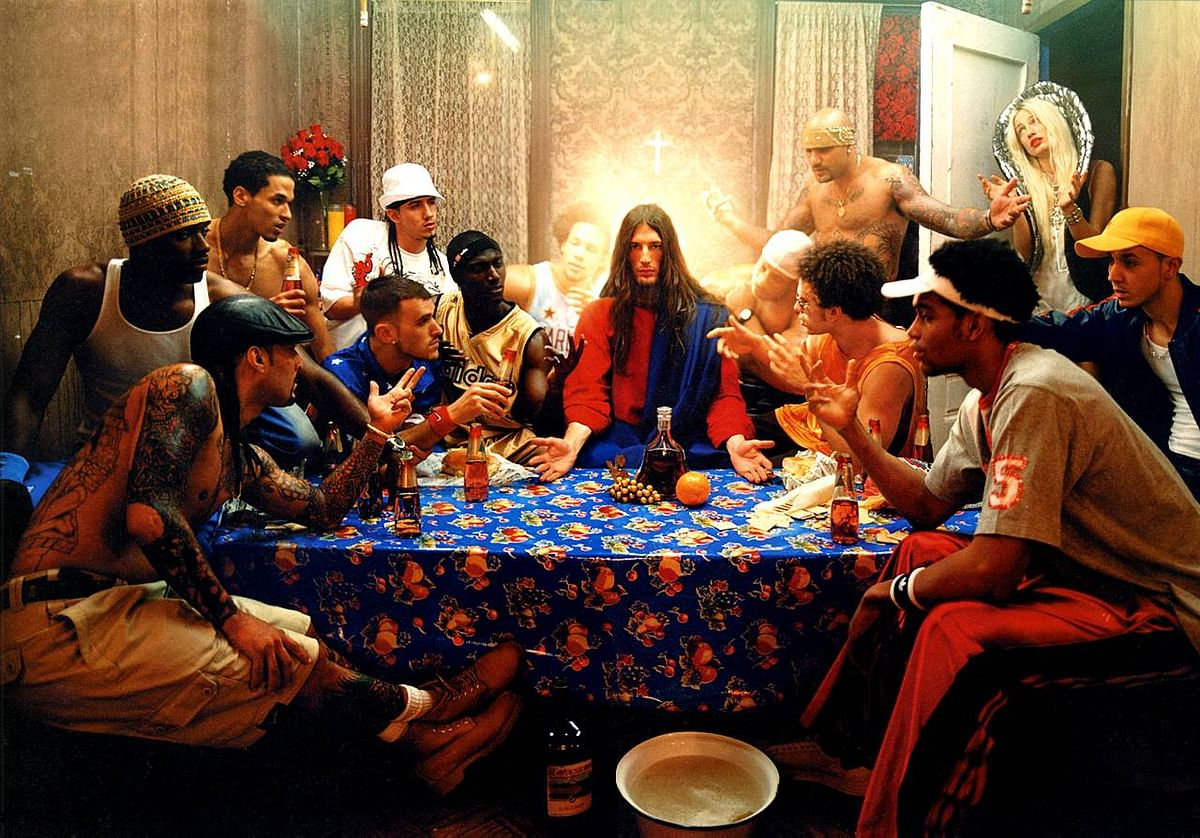Last Supper, 2003. This photo which is inspired from Leonardo da Vinci's painting shows a modernized life of Jesus. Jesus is placed in the center of the photograph and our attention is drawn towards him as all the other people are pointing and looking towards him.