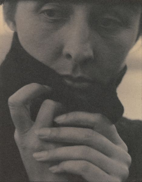 Georgia O'Keeffe, 1918. By using a tight composition Stieglitz includes only three quarters of her head and her fingers. The emphasis on her fingers is likely since she is a painter who uses her fingers to create art. Her eyes are turned away from the viewer creating a sense of mystery or her being lost in thought.