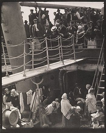 The Steerage, 1907. This photograph has people on the lower deck with a stairway leading to the upper deck. On the upper deck we see people looking down at the lower deck. The man with the circular hat is highlighted by the light. In addition to taking the viewers' gaze through the two decks the elements of the ship like the bridge, the mast, and the ladder create strong shapes.