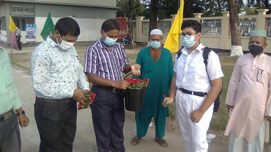 যশোর জেলা স্কুলের শিক্ষার্থীদের ফুল দিয়ে বরণ করে নিচ্ছেন শিক্ষকরা
