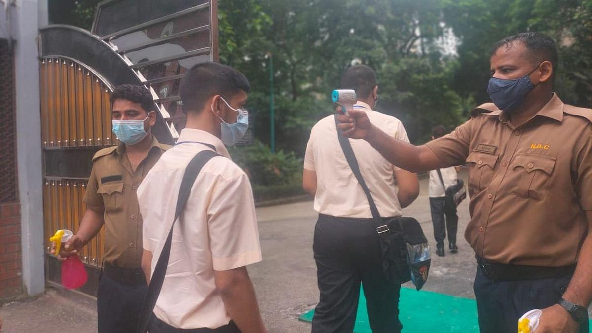 নটের ডেম কলেজের গেটে শিক্ষার্থীদের শারীরিক তাপমাত্রা পরীক্ষা করা হচ্ছে