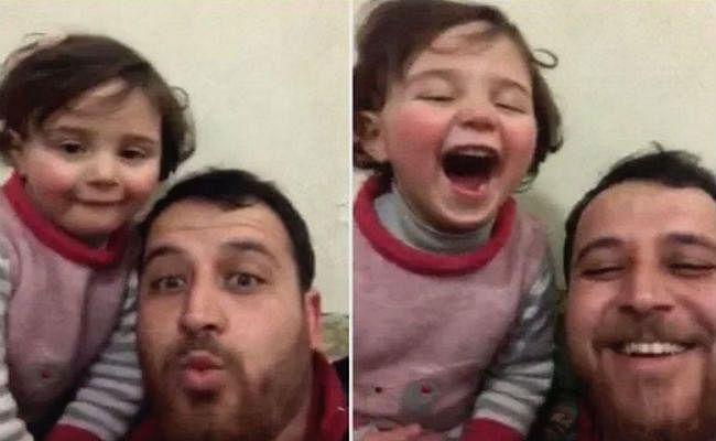 Viral : सीरिया में बम धमाकों की आवाज पर बेटी को खिलखिलाना सिखा रहा यह शख्स, देखें Video