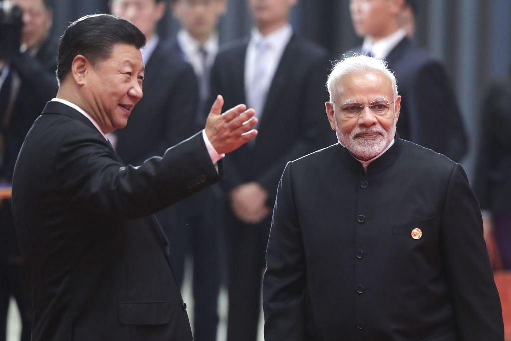 چین کے شہر کنگ ڈاؤ میں شنگھائی  تعاون تنظیم (ایس سی او) کی سربراہان کے 18 ویں اجلاس سے پہلے فوٹو سیسشن کے دوران وزیر اعظم نریندر مودی اور چینی صدر شی جن پنگ (10 جون2018)